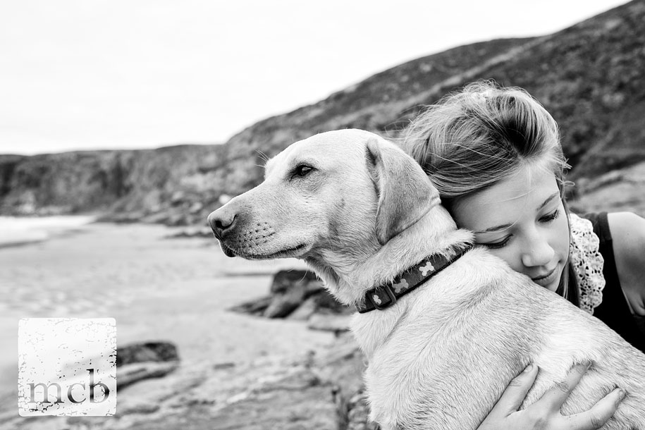 Girl hugs her dog on a beach