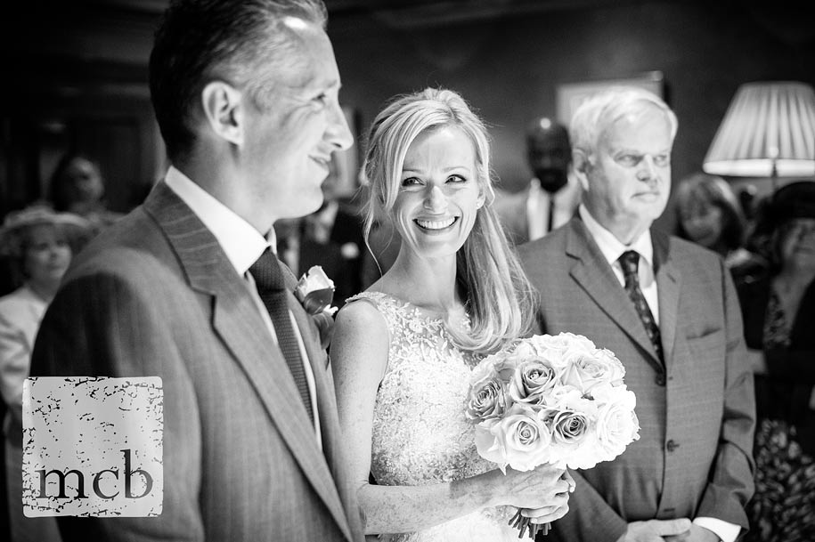 Bride smiles at the groom at The Waterside Inn wedding ceremony