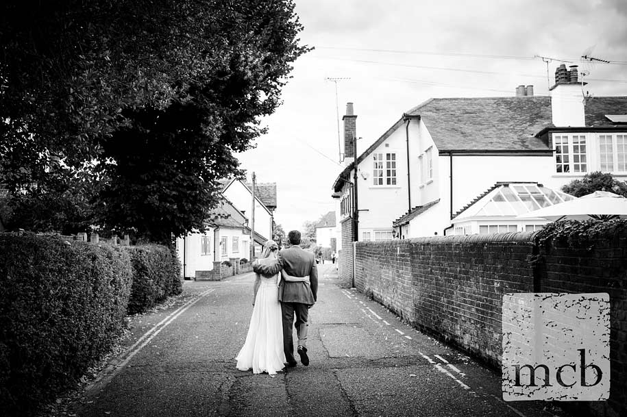 Bride and groom walk hand in hand at the Waterside Inn