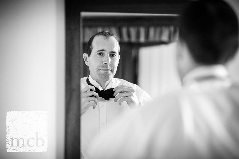 Groom ties his bow tie