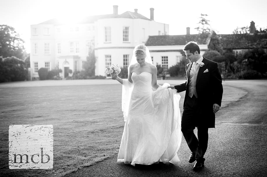 Bride and groom walk hand in hand at Newick park in Sussex