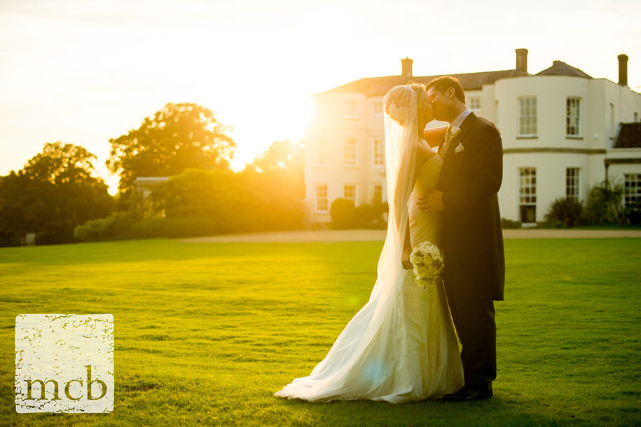 Bride and groom kiss in the evening sunlight at Newick park