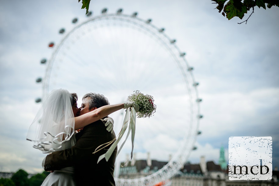 Bride and groom kiss in front of the London Eye