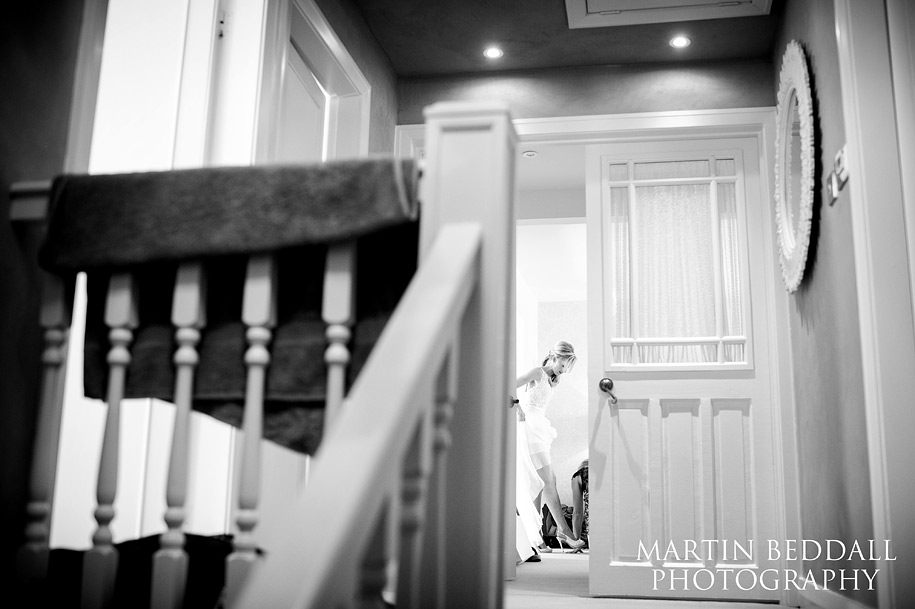 The bride slips on her weddding shoes spied through the door