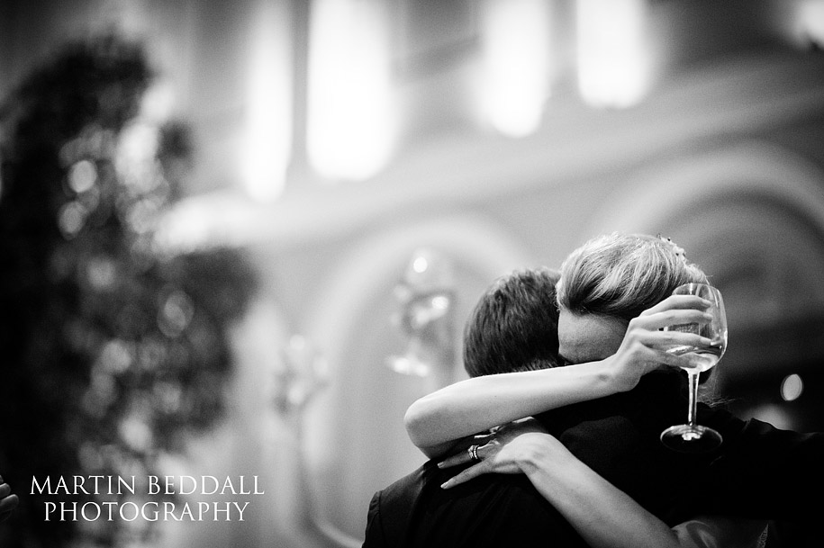 A bride hugs the groom after his emotional wedding speech