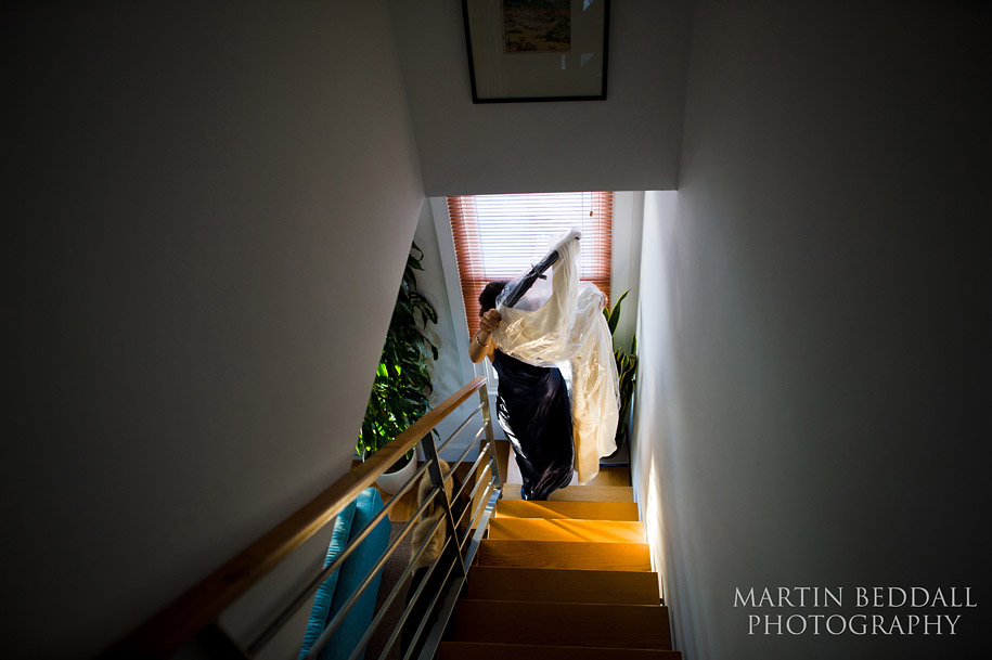 Bridesmaid carries the wedding dress up the stairs