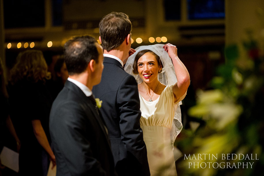 Bride smiles as she lifts up her veil