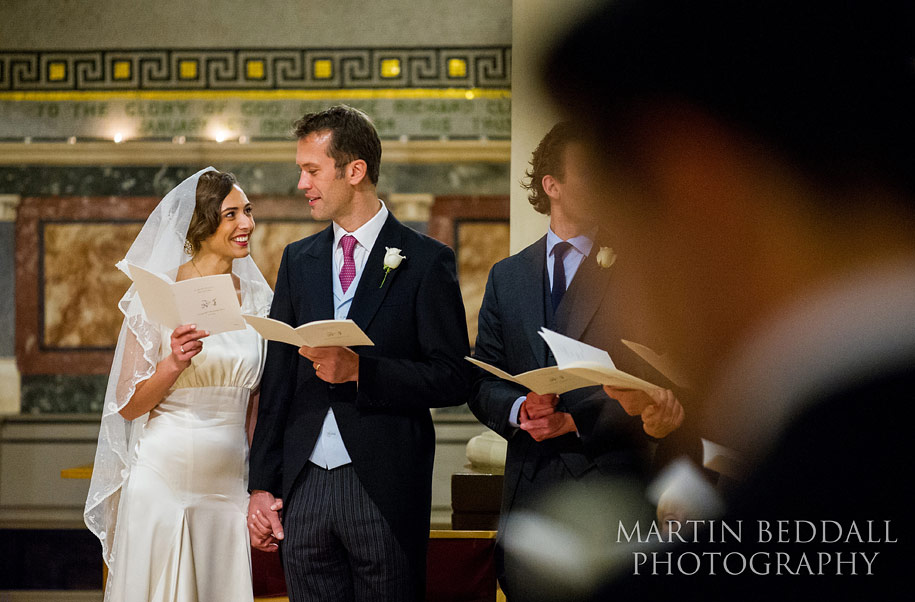 Brisde and groom exchange glances during a hymn