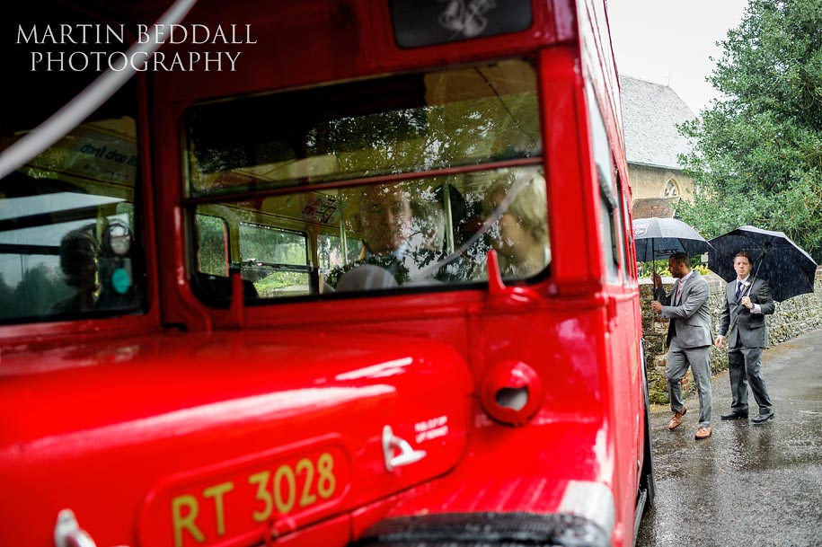 colour wedding photography in the pouring rain as guest board a red bus