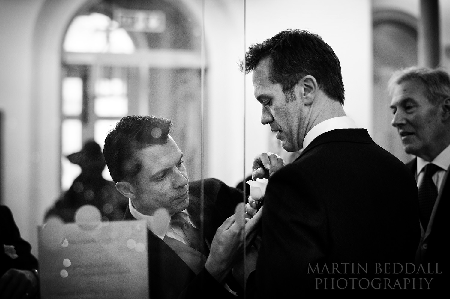 London winter wedding - helping the groom with his buttonhole