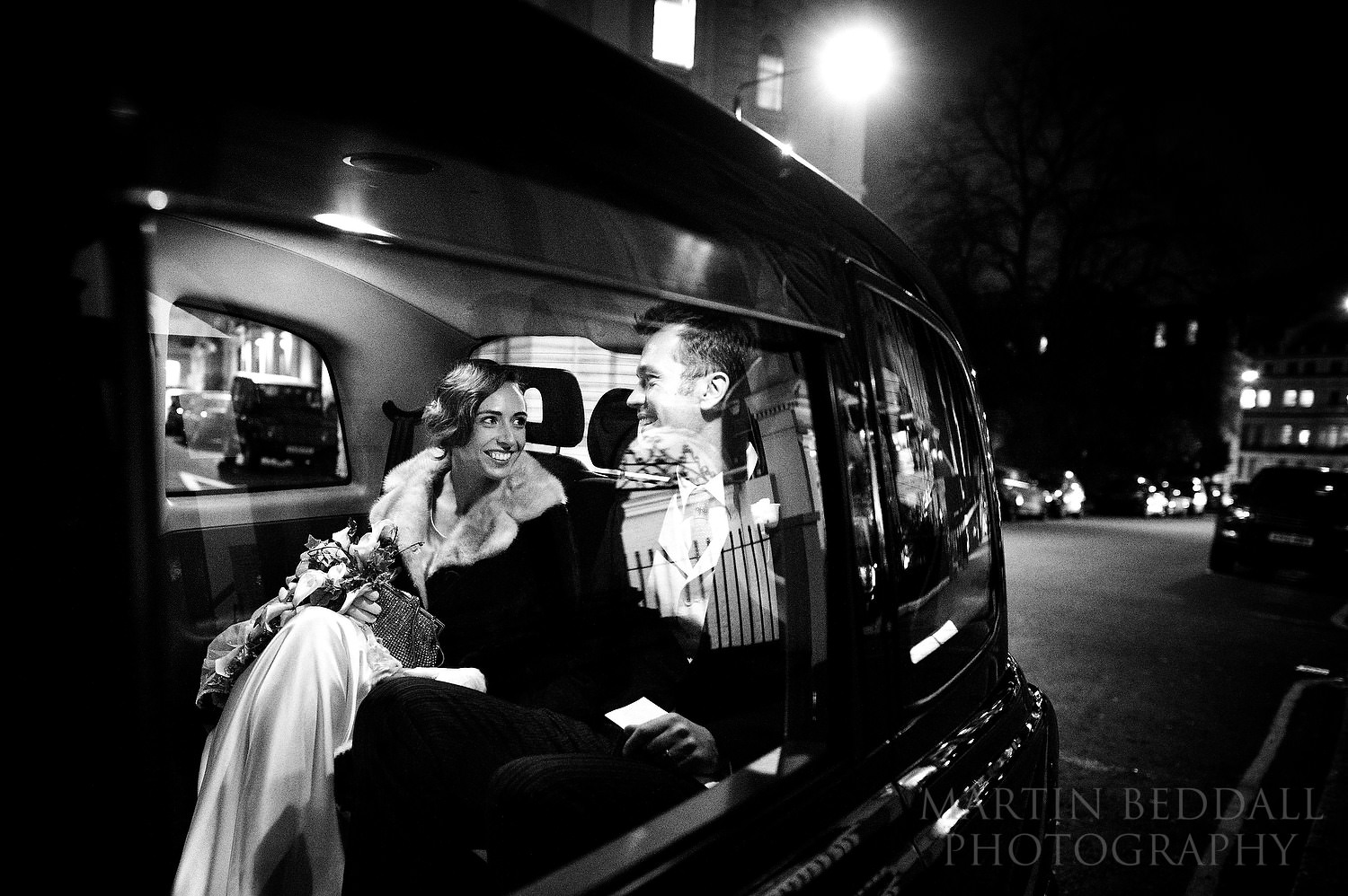 London winter wedding bride and groom leave the church in a black London taxi cab