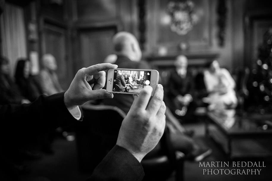 Guest photographs the wedding ceremony on his iphone