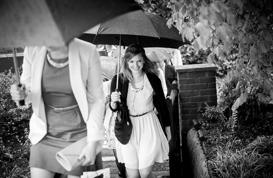 wedding guest arrives holding umbrella