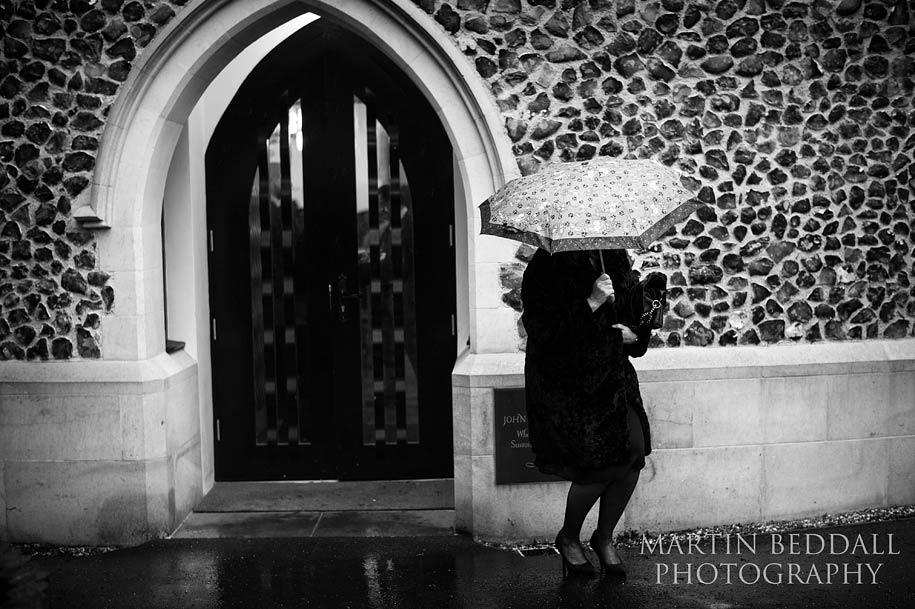 Guest crouches under an umbrella