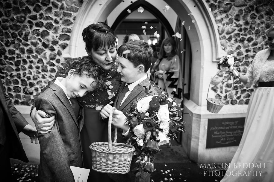 Bride hugs her sons outside the church