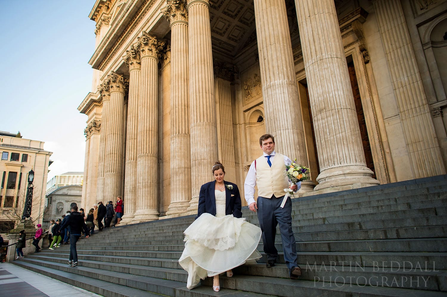 Bride and groom on the steps of St Paul's Cathedral after a winter wedding