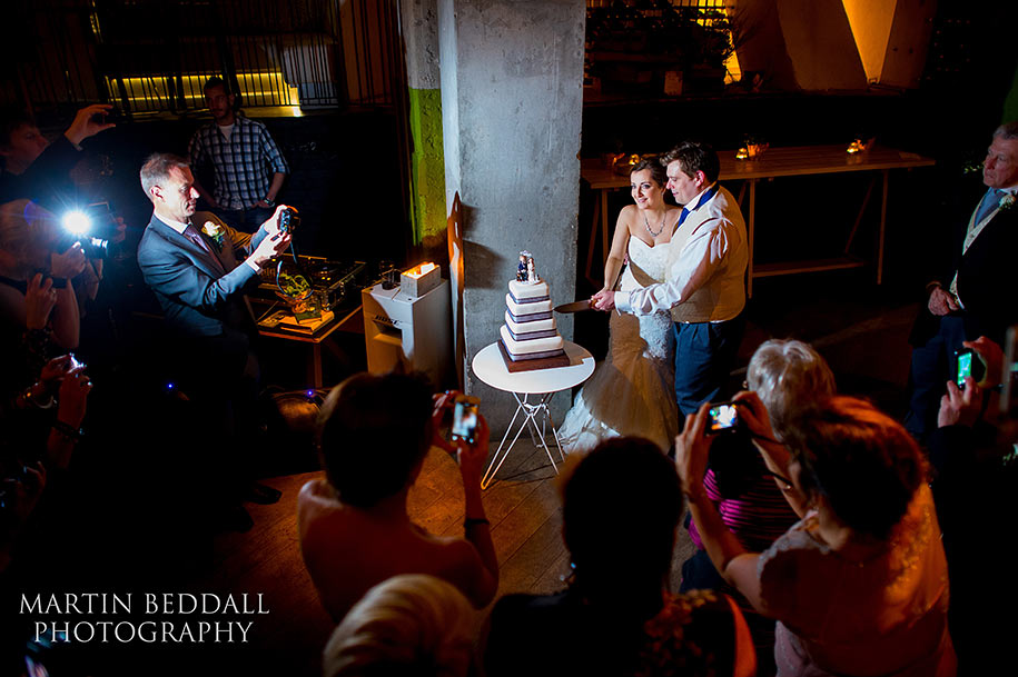 Bride and groom cut the wedding cake at The Folly Bar in London