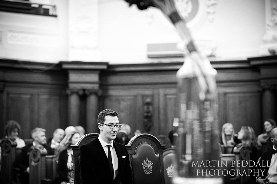 The groom sits in the council chamber waiting for the bride