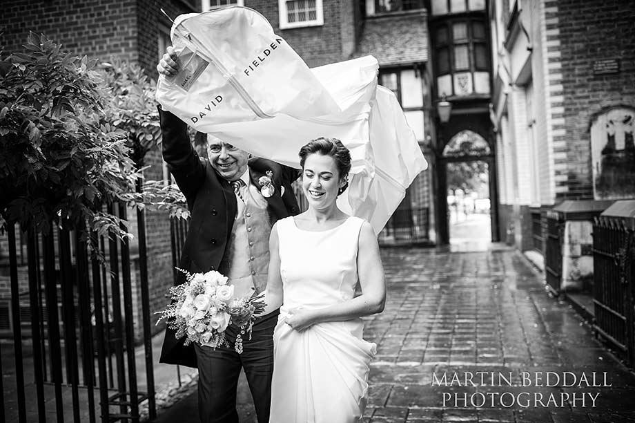 David Fielden dress cver helps keep the rain off the bride as she arrives at the church