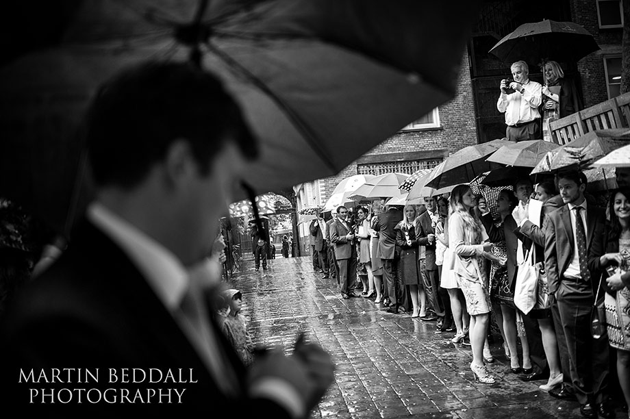 Wedding guests shelter fron the rain as they wait for the couple to exit the church