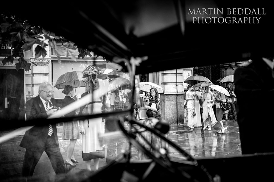 Wedding guests and umbrellas viewed through the wedding car