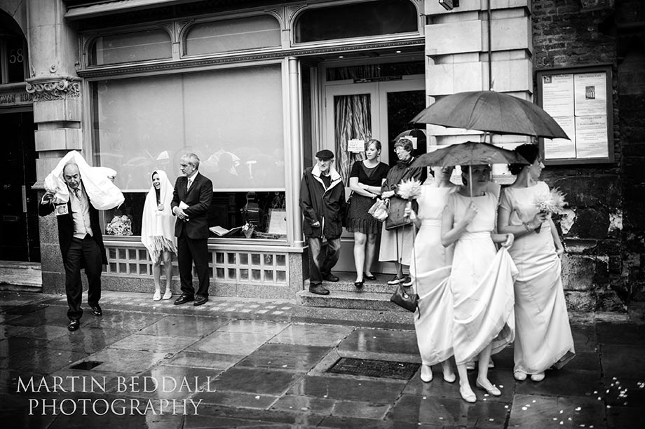 Wedding guests shelter from the rain