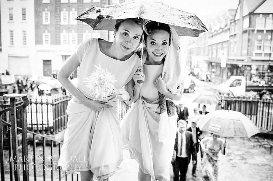 Two bridesmaids under an umbrella as they rain pours down