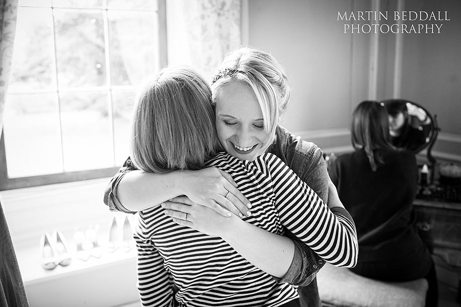 The bride hugs her mother as she gets ready