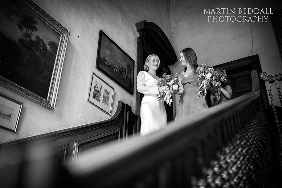 Bride and her twin sister at the top of the main staircase at Glemham Hall before the ceremony