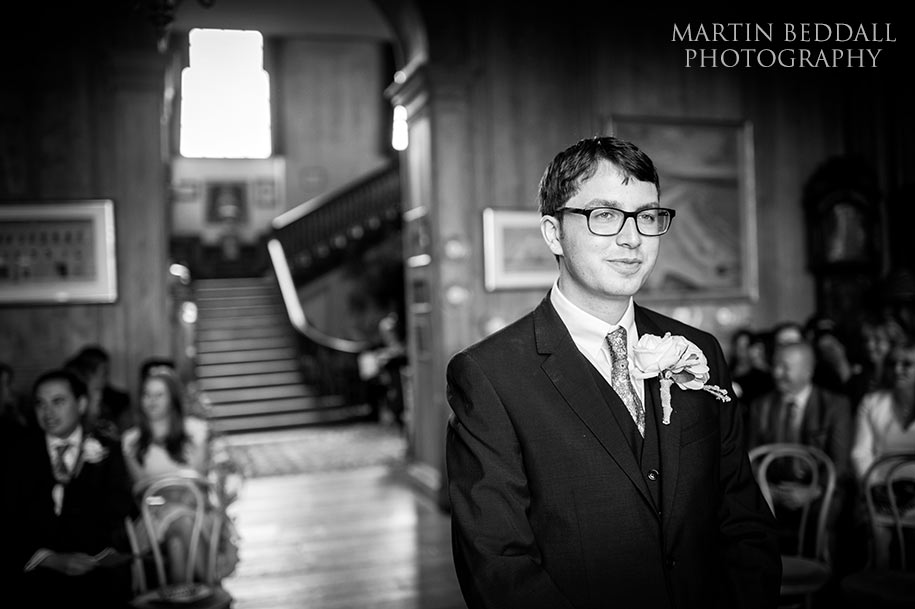 The groom waits in the Grand Hall at Glemham Hall