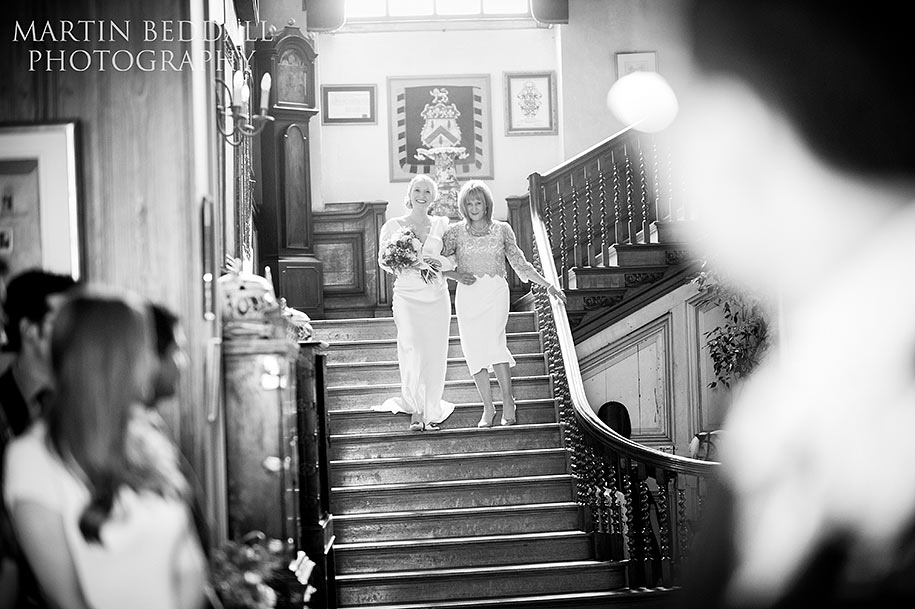 The bride descends the main staircase at Glemham Hall with her mother