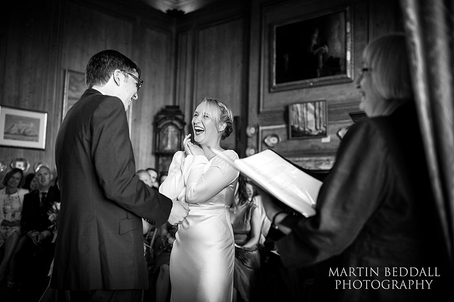 Laughing bride during the wedding ceremony at Glemham Hall