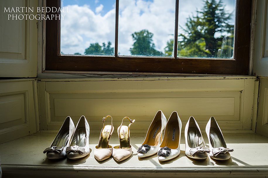 The bride and bridesmaid's shoes on a window sill in the sunshine