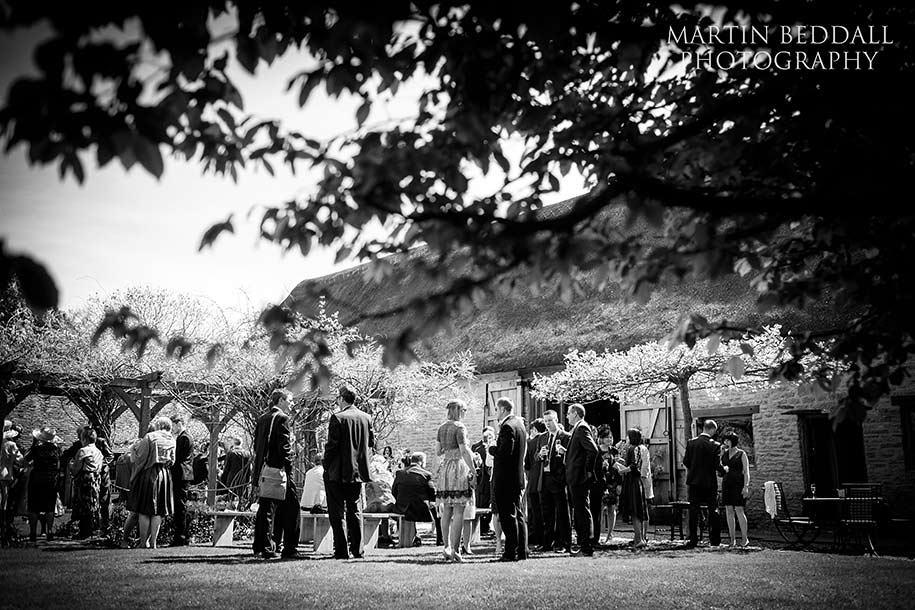 Wedding guests at the Tythe barn wedding reception in the sunshine