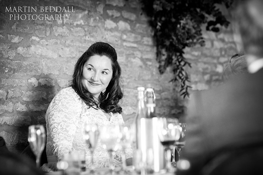 Bride smiles during her father's speech at Tythe barn wedding reception