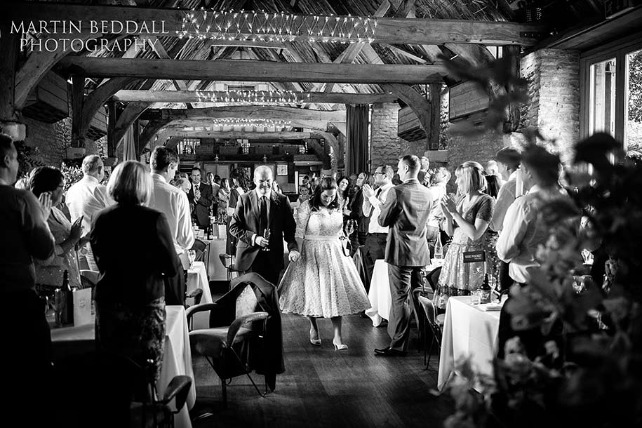 Bride and groom exit the Tythe barn to applause from guests.