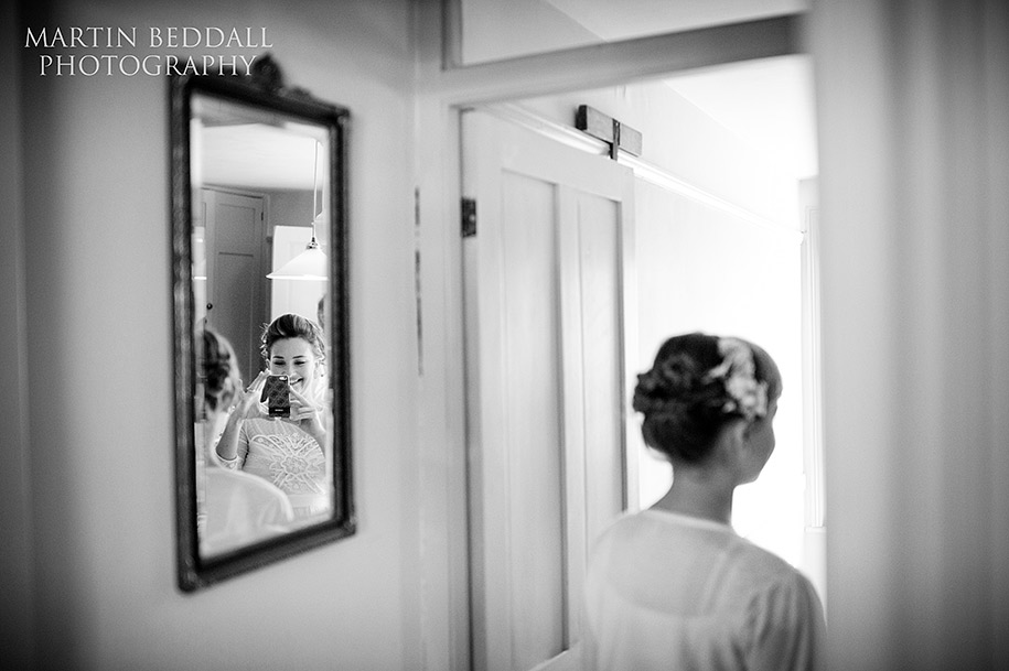 Bridesmaid photographs the flower girl in the mirror