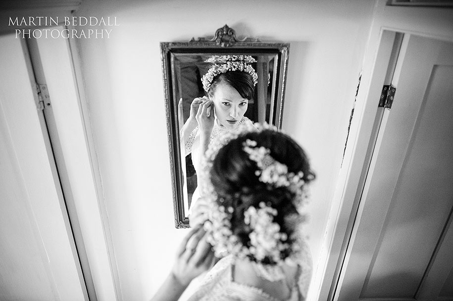 Bride adjusts her earrings in the mirror