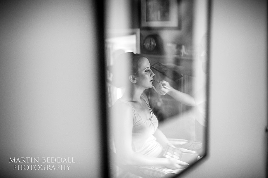 Bride having her makeup done reflected in a picture frame