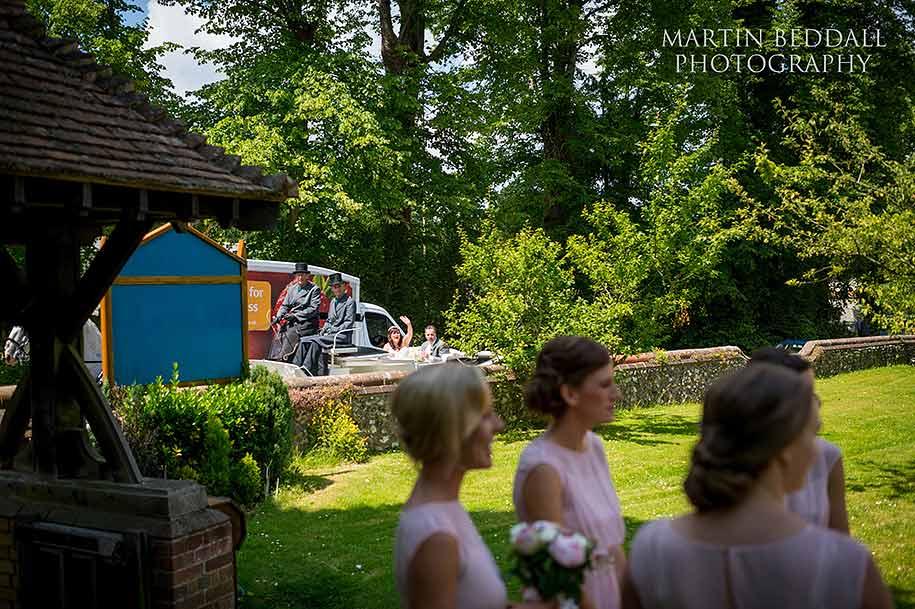 A passing bride waves at the bridesmaids