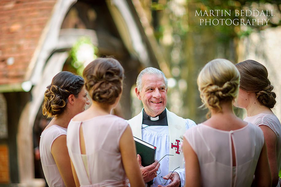 The vicar shares a joke with the bridesmaids
