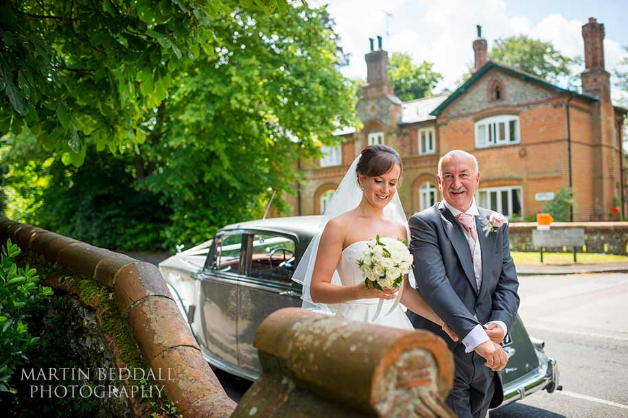 Bride walks from the wedding car with her father