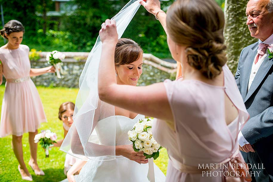 Bride's sister helps put on the veil
