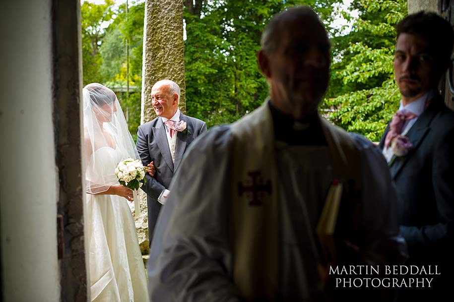 Bride an dher father share a joke before entering the church