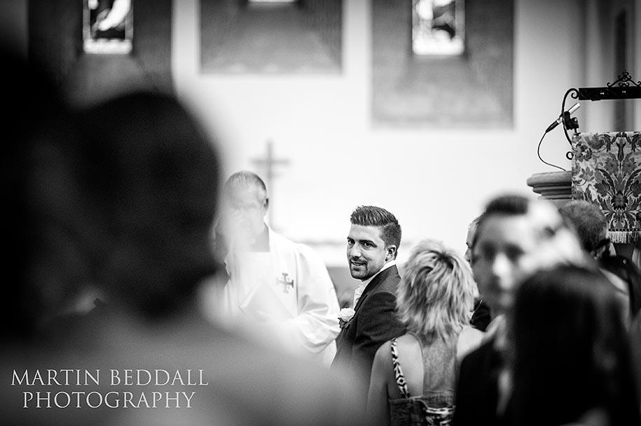 Groom looks down the aisle as the bride arrives