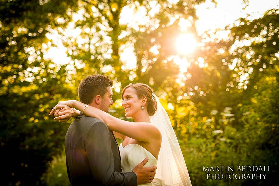 Bride and groom embrace in the evening sunlight