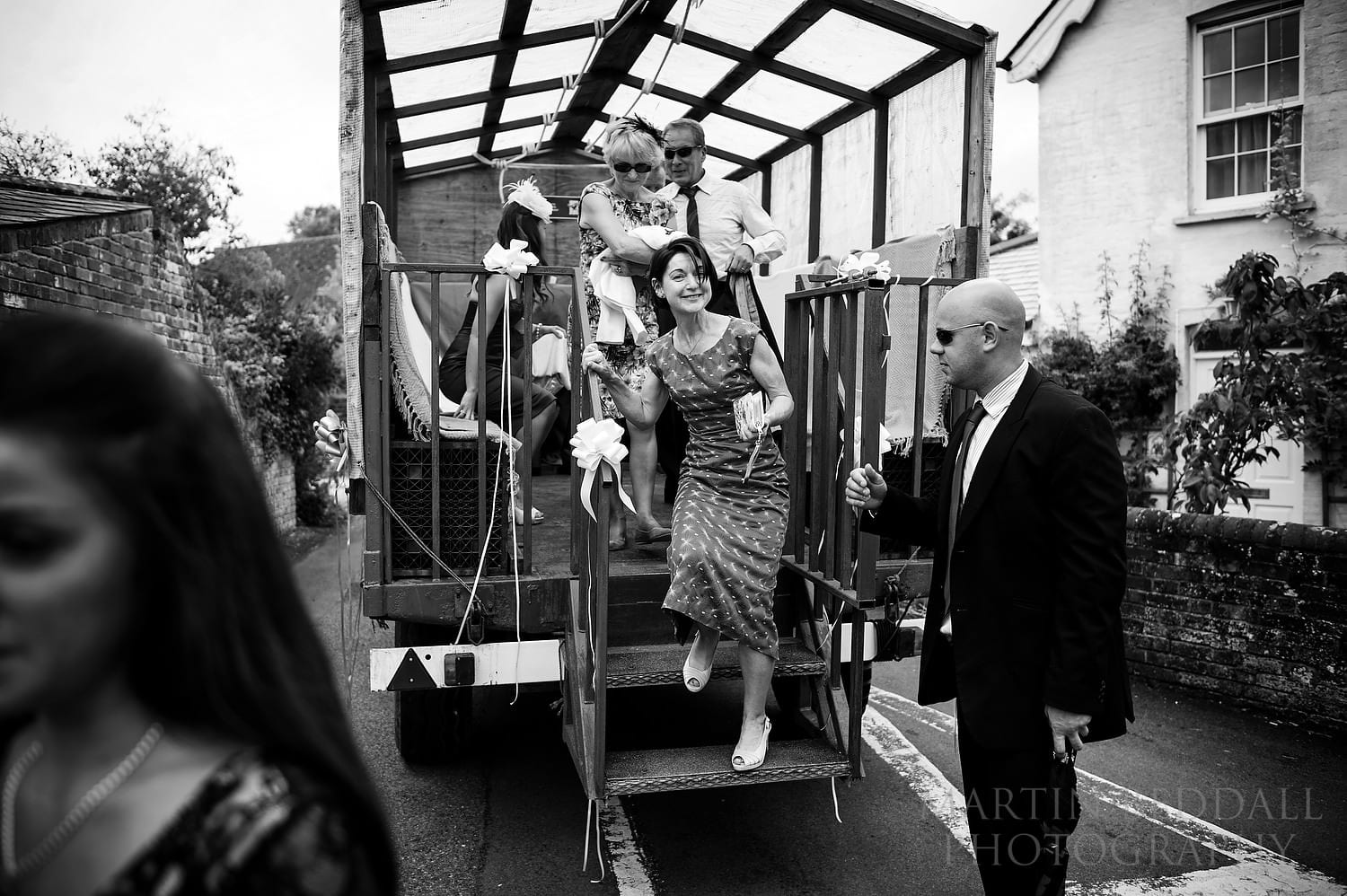 Guests arrive at the church in a farm trailer at this Berkshire wedding