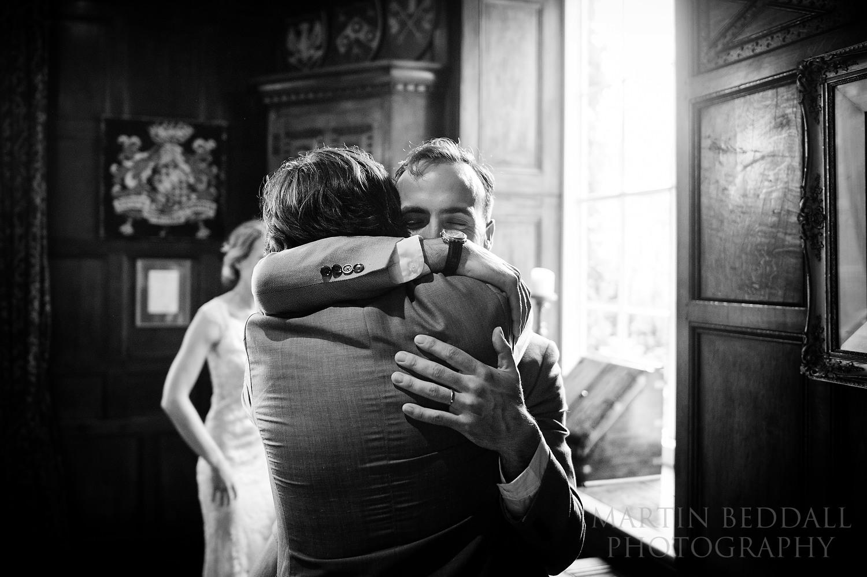 Groom and best man hug