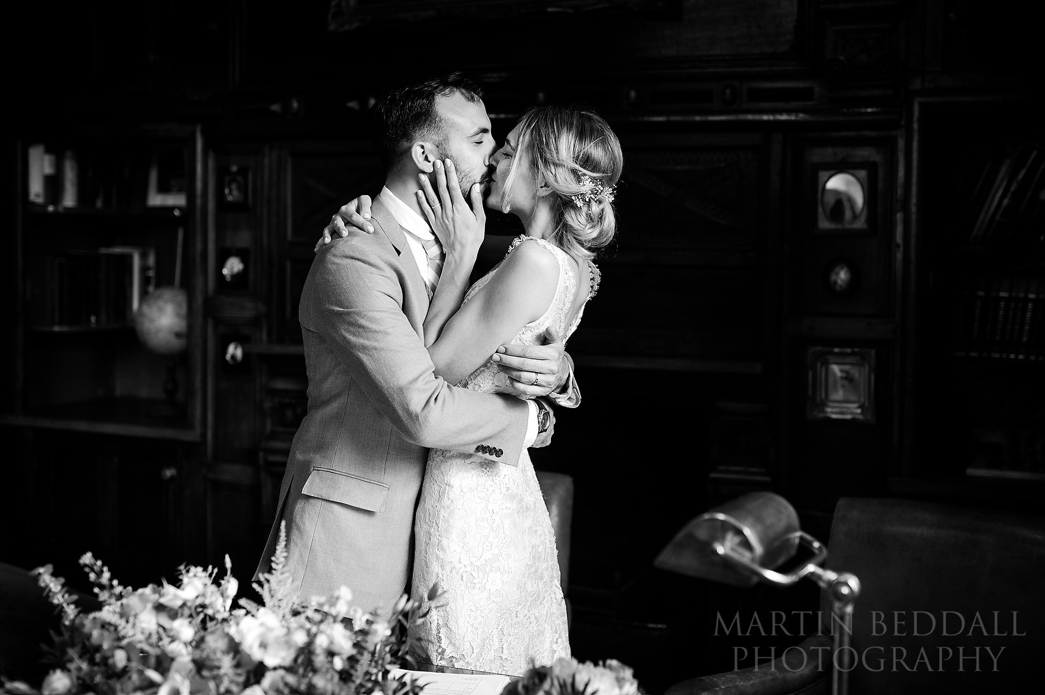 Bride and groom kiss in the Study at Dewsall Court