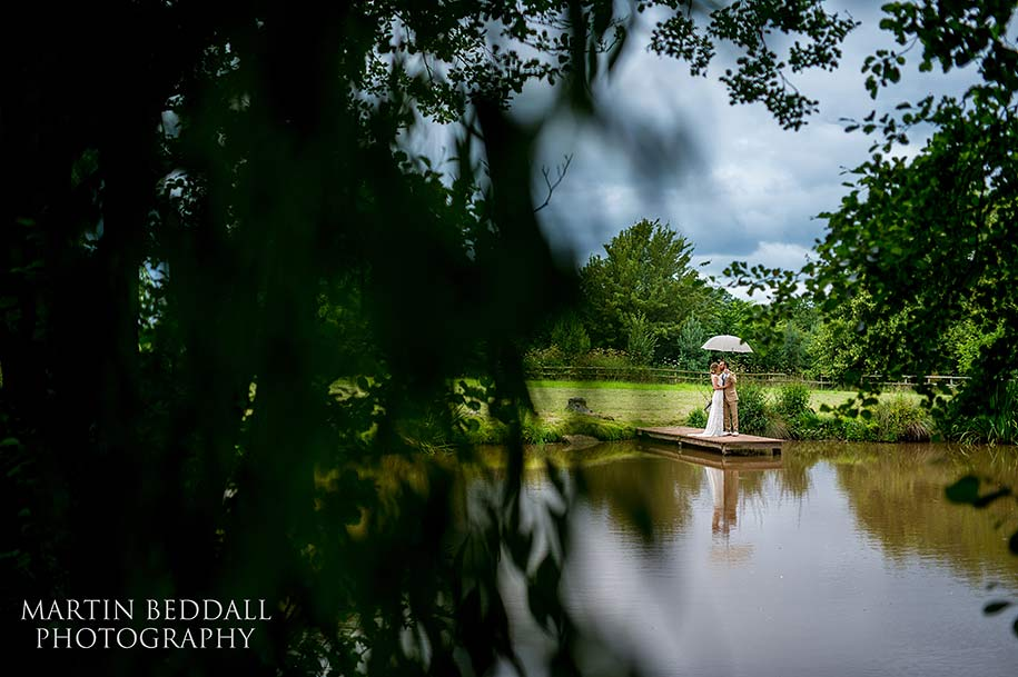 Bride and groom portrait by the lake at Dewsall Court